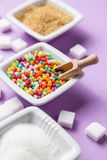 Different types of sugar with colored candy on white ceramic bow Royalty Free Stock Photo