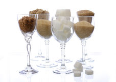 Different types of sugar in glasses on white. Royalty Free Stock Images
