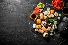 Different types of sushi, maki and rolls with soy sauce, ginger and green tea. On black rustic background stock image