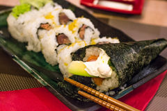 Different types of sushi, (spicy) salmon, avocado, philadephiia cheese and white rice wrapped in seaweed Stock Photo