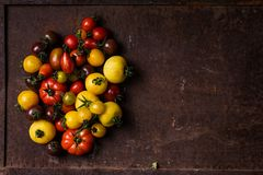 Different types of tomatoes on rusty background Stock Photo