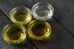 Different types of vegetable oil in glass bowls. Different types of vegetable oil of vegetable mustard and sesame seed, walnut, grape seeds in glass bowls. It is Stock Photos