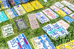 Different USA car retro license plates at flea market. Vintage vehicles registration numbers lay on grass at swap meet royalty free stock photography