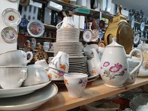 Different used vintage porcelain dishes.Second hand shop. Different used vintage porcelain dishes and other home related objects in flea market second hand shop Stock Photo