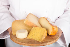 Different varieties of cheese on a board in the hands from the c Stock Photos