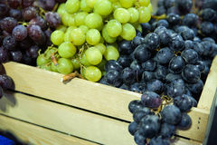 Different varieties of grapes in a wooden box. Beautiful healthy grapes, different varieties for table in a wooden pallet at the Farmer`s market. Fresh eating royalty free stock image