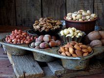 Different varieties of nuts on a wooden background - almonds, cashews, walnuts, hazelnuts, pistachios Stock Photos