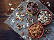 Different varieties of nuts on a wooden background - almonds, cashews, walnuts, hazelnuts, pistachios Stock Photo