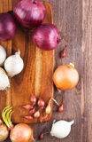Different varieties of onions. On a kitchen board and wooden surface Royalty Free Stock Image