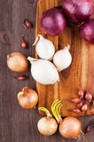 Different varieties of onions. On a kitchen board and wooden surface Stock Photo