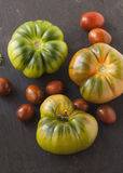 Different varieties of tomato on a black kitchen board. 