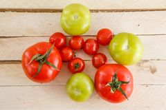 Different varieties of tomatoes on a wooden background royalty free stock images