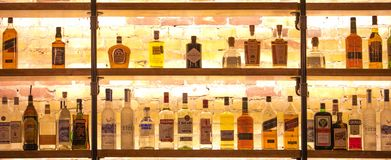 Different variety of alcohol in the bar. Or shelf with bright light at the back Stock Photos