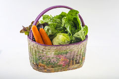 Different vegetables in the basket. Isolated over the white background Royalty Free Stock Images