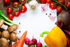 Different vegetables. Beautiful background healthy organic eating. Studio photography the frame of different vegetables and mushrooms with a white sheet of paper Stock Photos