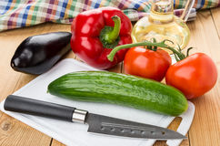 Different vegetables, bottle of oil, cutting board and knife Royalty Free Stock Photo