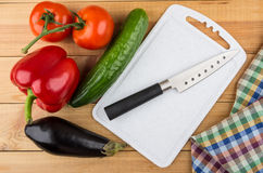 Different vegetables, cutting board and knife on table Stock Photos