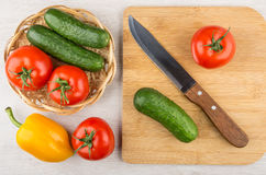 Different vegetables in wicker basket and on cutting board, knif Stock Photo