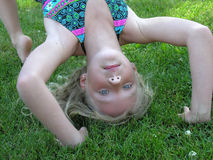 Different view. A young girl doing a backbend on the grass outside Stock Images