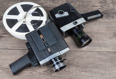 Different vintage amateur movie cameras and films on wooden surface. Two old vintage amateur film movie cameras powered by clockwork motor and electric motor and royalty free stock photo