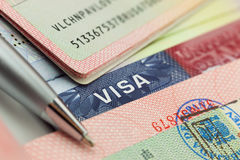Different visas and stamps in a passport background Stock Photos