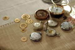Different watches and cogwheels, gearwheels in steampunk style on a table Stock Images