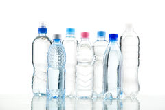 Different water bottles isolated on white. Close up Royalty Free Stock Photos