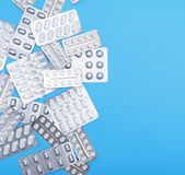 Different white tablets in a package are scattered on a blue bac Stock Photo