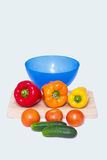 Different whole vegetables of different colors next to a bowl for a salad Stock Images