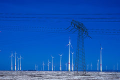Different windmills with power pole transmission line in winter landscape Stock Photography