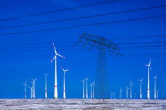 Different windmills with power pole transmission line in winter landscape Royalty Free Stock Photos