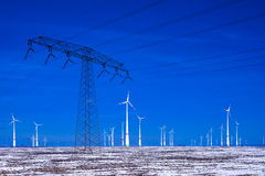 Different windmills with power pole transmission line in winter landscape Royalty Free Stock Images