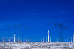 Different windmills with power poles transmission line in winter landscape Royalty Free Stock Photography