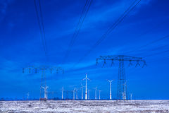 Different windmills with power poles transmission line in winter landscape Stock Images