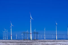 Different windmills with transmission line in winter landscape Stock Photos