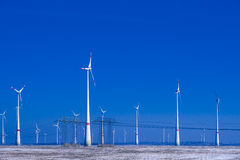 Different windmills with transmission line in winter landscape Stock Images