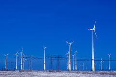 Different windmills with transmission line in winter landscape Royalty Free Stock Images