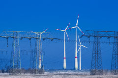 Different windmills with transmission line in winter landscape Stock Photography