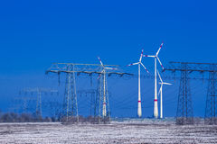 Different windmills with transmission line in winter landscape Royalty Free Stock Photography