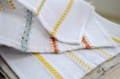Different yellow, orange and blue patterns of embroidery on white fabric. Different yellow, orange and blue patterns of embroidery on a white fabric royalty free stock photo