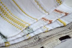 Different yellow, orange and blue patterns of embroidery on white and gray fabric stock photo