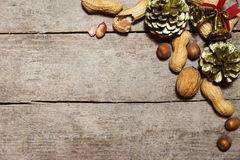 Differents nuts, fir cones and bells on wooden table Stock Images