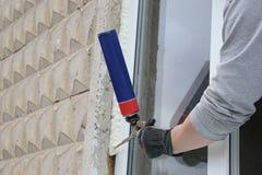Difficulté de la main du travailleur une fenêtre par la mousse de polyuréthane images libres de droits
