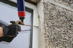 Difficulté de la main du travailleur une fenêtre par la mousse de polyuréthane photographie stock libre de droits