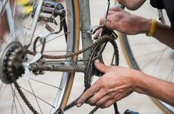 Difficulté de mécanicien la chaîne d'une bicyclette de vintage photo stock