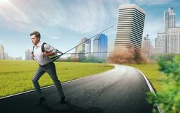 Difficult business way to success concept. Difficult and risky business way to success concept. Young businessman drags a skyscraper bound on a rope Stock Images