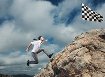 Difficult career and achievement business goal. Businessman climbs a mountain to get to the flag. Achievement business goal and Difficult career concept Stock Photos