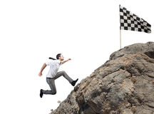 Difficult career and achievement business goal. Businessman climbs a mountain to get to the flag. Achievement business goal and Difficult career concept Royalty Free Stock Images