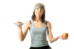 Difficult Choice. Between an unhealthy cookie and a healthy apple Stock Photo