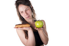 Difficult choice between cake and apple Stock Image